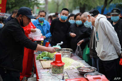 A vendor (L) demonstrates a food processer to customers at a market in Shenyang in China's northeastern Liaoning province on…