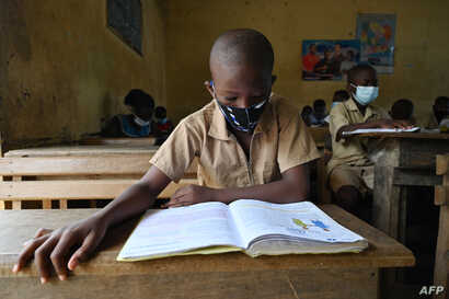 A child wears a face mask while he reads in a classroom at a primary school in the popular district of Attecoube in Abidjan on…