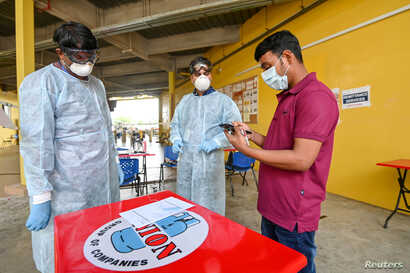 People wear protective face masks during remittance services set up at S11 Punggol migrant workers' dormitory during the…