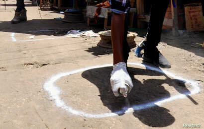 A worker marks a social distancing sign as a preventive measure against the spread of the coronavirus disease (COVID-19), at…