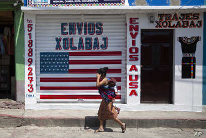 In this April 3, 2020 photo, a woman carrying a child walks past a closed courier business featuring a U.S. flag and the…