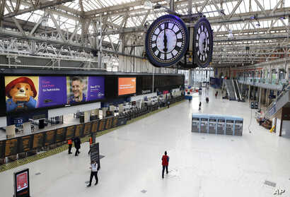 One of London's most famous rendezvous points is nearly empty under the Waterloo train station clock at 1800 in London, Friday,…