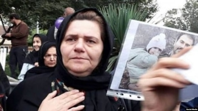 Farangis Mazloum, mother of jailed Iranian dissident Soheil Arabi, appears in this undated photo shared on social media, holding a photo of Arabi and his daughter while campaigning for his release.