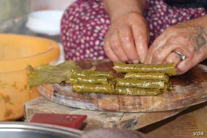 Ismahan says grape leaves rolled with rice and some yogurt is all she can afford for the day, in Istanbul, May 20, 2020. (VOA/Heather Murdock)