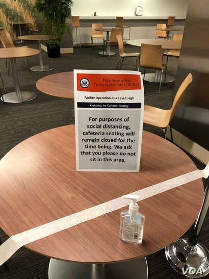 """A sign on one of the tables in the State Department cafeteria that have been blocked off for weeks calls for social distancing. Facility operation risk level is marked as """"high."""" (Nike Ching/VOA)"""