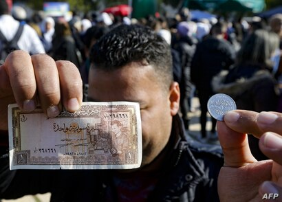 A man shows a Syrian pound in the form of a coin as well as a banknote, at a shopping festival in the Syrian capital Damascus…