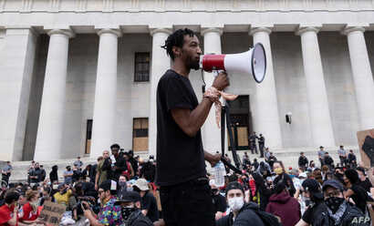 Protesters listen to a man speak as they gather peacefully in front of the Ohio Statehouse in Downtown Columbus, Ohio June 1,…