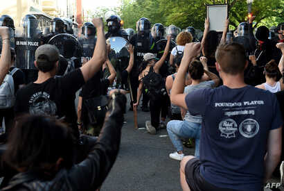 Protesters kneel and hold up their hands in front of a row of police during a demonstration against the death of George Floyd…