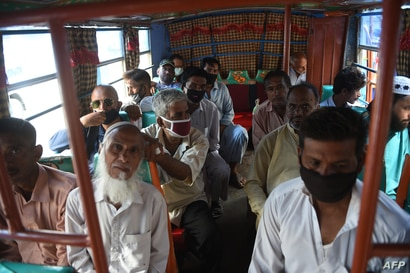 People sit in a mini bus after the government resumed public transport services, in Pakistan's port city of Karachi on June 3,…