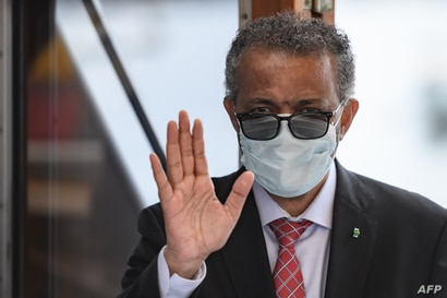World Health Organization (WHO) Director-General Tedros Adhanom Ghebreyesus wears a protective fave mask after leaving a…