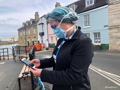 UK National Health Service employee Anni Adams looks at new NHS app to trace contacts with people potentially infected with the…