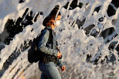 A woman wearing a face mask walks past a fountain amid the spread of the coronavirus disease (COVID-19), in San Diego,…