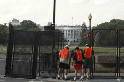 Workers remove a security fence Wednesday, June 10, 2020, near the White House in Washington. The fence was erected as protests…