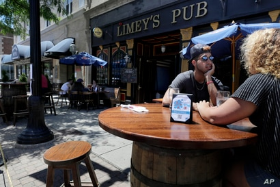 Diners are seated in an outdoor dining area on a sidewalk at Limey's Pub, in Norwood, Mass.  The…