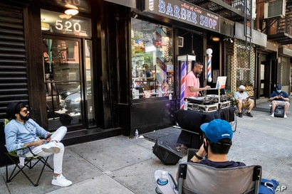 Customers wait on the sidewalk before receiving haircuts while a DJ plays outside Ace of Cuts barbershop, Monday, June 22, 2020, in New York.
