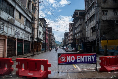 Indian youngsters play cricket in barricaded street during the reimposed lockdown in Gauhati, India, Monday, June 29, 2020…
