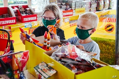 Children wear face masks as they pick out fireworks at Wild Willy's Fireworks tent in Omaha, Neb., Monday, June 29, 2020, ahead…