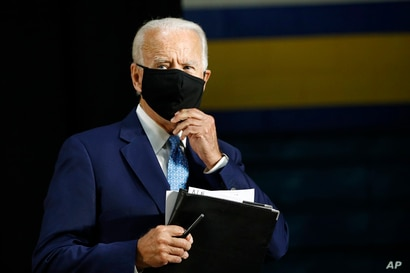 Democratic presidential candidate, former Vice President Joe Biden puts on a face mask to protect against the spread of the new…