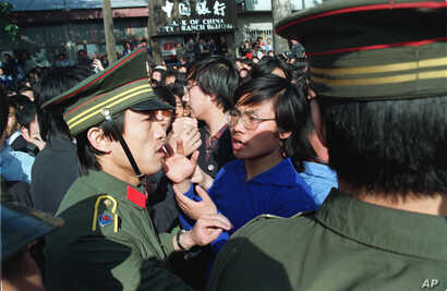 A Beijing University student leader argues with a policeman about the students' right to march as they are told not to march…