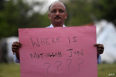 A journalist holds a placard during a protest against the seized of a Pakistani journalist Matiullah Jan in Islamabad on July…