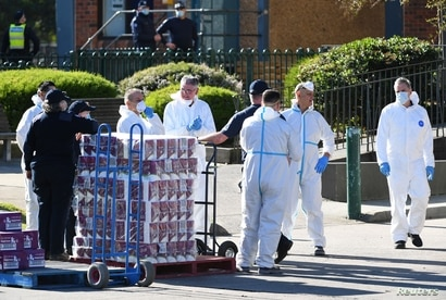 Response personnel prepare to distribute goods to residents inside a public housing tower, locked down in response to an…
