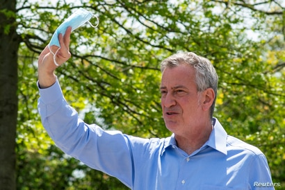 FILE PHOTO: New York City Mayor Bill De Blasio speaks to people as he gives away face masks for using on public spaces to…