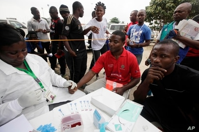 FILE - A doctor takes an AIDS/HIV blood test from an athlete during the 18th National Sports Festival in Lagos, Nigeria.