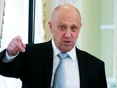 FILE - In this Tuesday, Aug. 9, 2016 file photo, businessman Yevgeny Prigozhin, left, gestures on the sidelines of a summit…