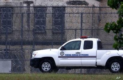A Federal Bureau of Federal Prisons truck drives past barbed wire fences at the Federal Medical Center prison in Fort Worth,…
