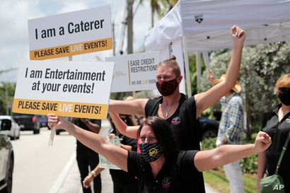 Jennifer Degroff, owner of the Tipsy Rose Bar and Catering Services, protests in support of the live events industry receiving…