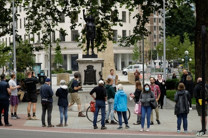 People look at a statue of a Black Lives Matter protester by British artist Marc Quinn erected in the spot once occupied by the statue of a slave trader in the English city of Bristol.