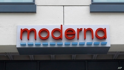 A sign marks an entrance to a Moderna, Inc., building, Monday, May 18, 2020, in Cambridge, Mass. Moderna announced Monday that…