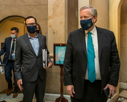 White House chief of staff Mark Meadows, right, and Treasury Secretary Steven Mnuchin, arrive at the office of House Speaker…