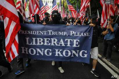 Protesters hold a banner and wave US national flags as they march from Chater Garden to the US consulate in Hong Kong on September 8, 2019, to call on the US to pressure Beijing to meet their demands and for Congress to pass a recently proposed bill…