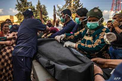 EDITORS NOTE: Graphic content / Medical volunteers hold a bag carrying the body of a man killed during Turkish shelling in the…