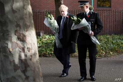 Britain's Prime Minister Boris Johnson walks with Chief Constable of Essex Police, Ben-Julian Harrington, as they prepare to…