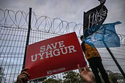 "A supporters of China's Muslim Uighur minority holds a placard reading ""Save Uighur"" as a boy waves the flag of East Turkestan…"