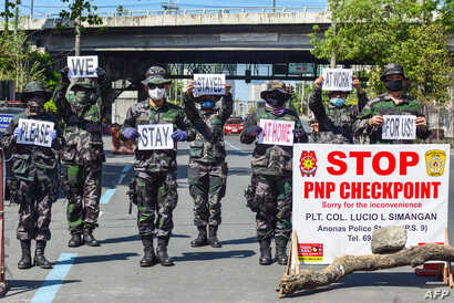 Police personnel hold up placards reminding people to stay at home amid concerns of the spread of the COVID-19 coronavirus in…