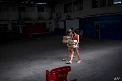 Young women carry boxes with donations of basic food supplies distributed by an NGO to people suffering during the novel…