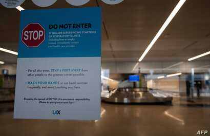 A sign about stopping the spread of COVID-19 is posted at Los Angeles International Airport (LAX) during the outbreak of the…