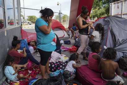 In this Aug. 30, 2019, photo, a group of Mexican asylum seekers wait near the Gateway International Bridge in Matamoros, Mexico. Pregnant women face special hazards in Mexico because places where migrants wait to enter the U.S. often don't have…