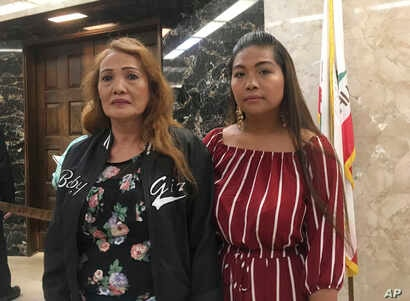 Savun Yong, left, the mother of Borey Ai, and his sister-in-law, Jennie Ou, right, pose while attending a rally by advocacy groups calling for California Gov. Jerry Brown to grant pardons to Ai and others facing deportation to Cambodia, Wednesday,…