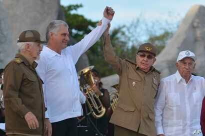 Cuba's President Miguel Diaz-Canel, second left, and former President Raul Castro, raise their arms in unison during an  event celebrating Revolution Day, accompanied by Commander of the Cuban Revolution Ramiro Valdes, left, and Jose Ramon Machado…