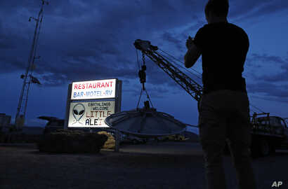 """A man takes a picture of a sign at the Little A'Le'Inn during an event inspired by the """"Storm Area 51"""" internet hoax, Thursday, Sept. 19, 2019, in Rachel, Nev. Hundreds have arrived in the desert after a Facebook post inviting people to """"see them…"""