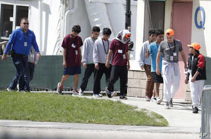 FILE- In this July 15, 2019 file photo, migrant children walk on the grounds of the Homestead Temporary Shelter for…