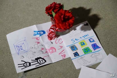 Flowers and cards are placed in front of Saugus High School in the aftermath of a shooting on Thursday, Nov. 14, 2019, in Santa…