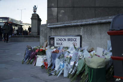 Tributes placed by the southern end of London Bridge in London, Monday, Dec. 2, 2019. London Bridge reopened to cars and…