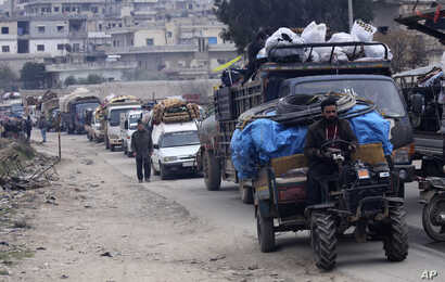 Syrians drive through the city of al-Mastouma, in Idlib province, as they flee a government offensive, Tuesday, Jan. 28, 2020…