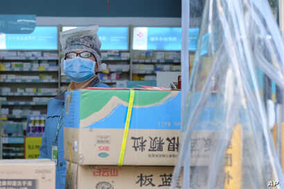 A clerk wearing a face mask and a plastic bag stands in a pharmacy in Wuhan in central China's Hubei Province, Friday, Jan. 31,…