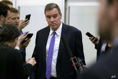 Sen. Mark Warner, D-Va., talks to reporters as he walks to attend the impeachment trial of President Donald Trump on charges of…